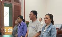 Cựu cán bộ công an Phạm Quang Tiến (áo xanh, thứ 3 phải sang) tại phiên tòa,