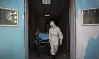 Nhân viên y tế di chuyển một bệnh nhân Covid-19 tại bệnh viện ở Vũ Hán. (Ảnh: AP)