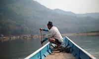 Một người dân Lào chèo thuyền ở khúc sông dự kiến sẽ được xây đập thủy điện ở Luang Prabang. (Ảnh: Reuters)