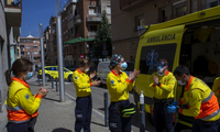 Các nhân viên y tế Tây Ban Nha khử trùng tay sau khi vận chuyển một bệnh nhân hôm 6/4. (Ảnh: AP)