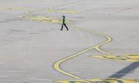Một nhân viên đi trên đường băng của sân bay quốc tế ở Bắc Kinh ngày 9/3. (Ảnh: Reuters)