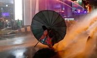 Một người biểu tình dùng ô chống lại vòi rồng của cảnh sát. (Ảnh: Reuters)