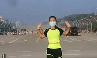Người phụ nữ đang tập thể dục trước dàn xe quân sự