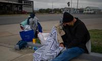 Một cặp vợ chồng người Texas ngồi sát bên nhau bên lề đường. Họ cho biết họ bị mất nhà sau khi mất việc năm 2020 vì đại dịch COVID-19. (Ảnh: Reuters)
