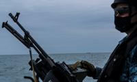 Một lính Nga tuần tra trên biển Azov ngày 19/4, cách đó không xa là một tàu của Nga. (ảnh: NYT)