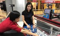 Nhân viên siêu thị đang đếm các chai nước loại 1,5 lít trong xe đẩy của một khách hàng