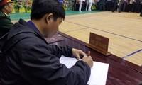 Người dự lễ viếng ghi sổ tang trong buổi tiễn đưa 22 liệt sĩ về nơi an nghỉ cuối cùng.