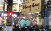 Tiệm trà sữa bán mang về rất đông người xếp hàng chờ mua đứng rất gần nhau