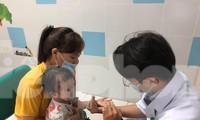 Bác sĩ khám cho một trẻ bị mắc tay chân miệng