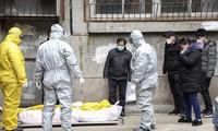 Công nhân nhà tang lễ thu dọn xác của một người bị nghi là đã chết vì dịch coronavirus từ một tòa chug cư ở Vũ Hán, tỉnh Hồ Bắc, Trung Quốc ngày 1/2 (AP)