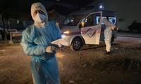 Các quan chức y tế và một xe cấp cứu chờ đợi để thu thập các bệnh nhân COVID-19. (Rasmei News)