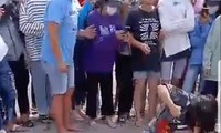 Nhiều người đứng bên ngoài cổ vũ 2 nữ sinh đánh nhau.