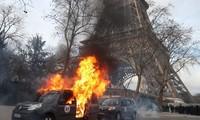 Xe quân sự chống khủng bố bị người biểu tình đốt gần Tháp Eiffel hôm 9/2. Ảnh: AFP