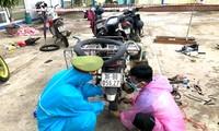 Các chiến sĩ Công an huyện Ngọc Hồi, Kon Tum sửa xe giúp người dân từ phía Nam về quê qua địa bàn