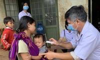 Bác sĩ kiểm tra thân nhiệt của các em nhỏ ở xã Hải Yang, huyện Đắk Đoa