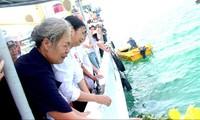 Bà Doãn Thị Mai và chị Doãn Thị Thu xúc động trong lễ thả hoa tưởng niệm các liệt sĩ tàu C235 trên biển.