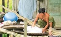 Một người A Rem đang đưa bao gạo còn lại ra phơi hi vọng còn dùng được trong mấy ngày tới.