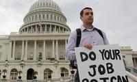 """Một nhân viên liên bang Mỹ đứng ngoài tòa nhà Quốc hội giơ tấm biển có dòng chữ: """"Hãy làm việc của các ông để tôi có thể làm việc của tôi"""", sau khi chính phủ Mỹ bị đóng cửa tạm thời. Ảnh: Larry Downing."""