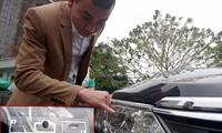 Chủ xe thử độ bám dính của thẻ thu phí không dừng dán trên đèn xe. Ảnh: PT.