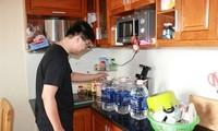 Một gia đình tại chung cư TSQ Euroland dự trữ số nước ít ỏi vừa lấy được từ xe stec.