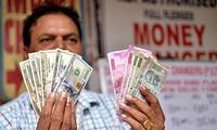 Vì một số lý do, Ấn Độ cũng muốn giảm phụ thuộc vào USD. Trong ảnh: Một người làm nghề đổi tiền ở thủ đô Delhi. Ảnh: Xinhua
