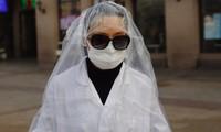 Một hành khách mặc áo nylon kín người đi bên ngoài ga tàu ở Bắc Kinh hôm 11/2ảnh: EPA-EFE