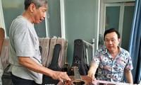 Nghệ sĩ Chí Tài và nghệ nhân làm đàn Ngọc Thức bên cây ghi ta (Ảnh tư liệu của gia đình nghệ nhân)