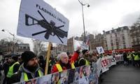 Người biểu tình 'Áo vàng' mang theo biểu ngữ phản đối, cùng ảnh của các nạn nhân bị thương khi đụng độ với cảnh sát