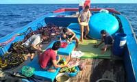 Ngư dân Nguyễn Đình Sang (áo đỏ) đang sắp mâm cúng trước giờ tàu chạy vào vòng Nguyệt Thiềm. Ảnh: Văn Chương