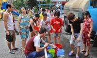 Người dân Linh Đàm, Hà Nội xếp hàng lấy nước sạch từ xe tec nước chở đến. Ảnh: như ý