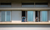Các bệnh nhân nhìn ra từ cửa sổ bệnh viện Kim Ngân Đàm ở Vũ Hán. Ảnh: EPA-EFE