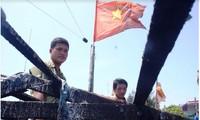 Thuyền trưởng Bùi Văn Phải và ngư dân Phạm Quang Thạnh bên con tàu cháy. Ảnh: LÊ VĂN CHƯƠNG