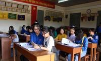 """""""Giáo viên"""" áo xanh nhiệt tình chỉ dẫn cho các em học sinh kiến thức môn tiếng Anh. Ảnh: Giang Thanh"""