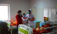 Cán bộ y tế hướng dẫn người dân đeo khẩu trang đúng cách