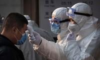 Nhân viên y tế Trung Quốc kiểm tra thân nhiệt một hành khách ở sân bay. (Nguồn: AP)