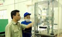 Kỹ sư Nguyễn Tiến Hưng (trái) kiểm tra thiết bị sản xuất sản phẩm quốc phòng tại Xí nghiệp II .   Ảnh: PV