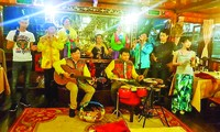 Tác giả bài viết đánh đàn ghi ta trên thuyền phục vụ khách du lịch trên sông Sài Gòn
