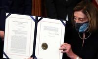 Chủ tịch Hạ viện Nancy Pelosi trưng ra văn bản thông qua việc luận tội tổng thống Trump sau khi ký phê chuẩn ảnh: Reuters