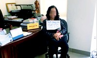 Một phụ nữ cầm biển đòi nợ tại phòng làm việc của Giám đốc Sơn