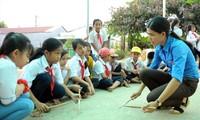 Cô Thạch Thị Bút Pha hướng dẫn học sinh tập gõ, đánh các bàitrống Đội trên nền sân trường. Ảnh: Xuân Tùng