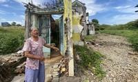 Bà Nguyễn Thị Giáp (80 tuổi) bên căn nhà bị đập loang lổ và lau sậy cao lút đầu người ở Thủ Thiêm