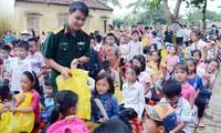Đại úy Trần Duy Văn trao quà tặng học sinh ở xã Cẩm Lương, huyện Cẩm Thủy (Thanh Hóa) bị ảnh hưởng nặng nề do lũ lụt, năm 2018