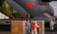 Các nhân viên y tế Philippines dỡ lô vắc-xin do máy bay quân sự Trung Quốc đưa đến ảnh: Reuters