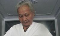 Mẹ Muộn với tấm áo của con ảnh: Trần Tuấn (chụp năm 2011)