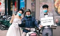 Chú rể Nghiêm Đình Đăng và cô dâu Phạm Ngọc Vy tặng khẩu trang miễn phí cho người dân Hà Nội. ảnh: Windy Wedding.