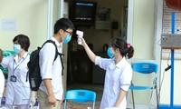 Tình nguyện viên đo thân nhiệt cho thí sinh tại kì thi tốt nghiệp THPT 2020