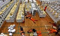 Các nhân viên nằm nghỉ tại chỗ trong giờ giải lao trong khi chuẩn bị tài liệu bầu cử. Ảnh: Reuters