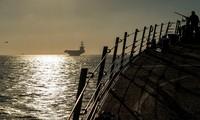 Quân nhân Mỹ trên tàu khu trục USS Bainbridge, phía xa là tàu sân bay USS Abraham Lincoln trên eo biển Gibralta ngày 13/4 ảnh: Reuters/Sputnik