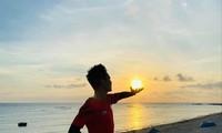 """Đỗ Quốc Luật """"nâng"""" mặt trời trong buổi bình minh ở đảo Lý Sơn . Ảnh: NVCC"""