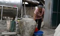 Bà Vang Thị Kim chắt chiu từng giọt nước quý giá mà bà đi xin được Ảnh: PV